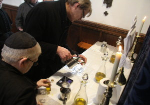The clergy collect the newly blest Holy Oils for use in their parishes.